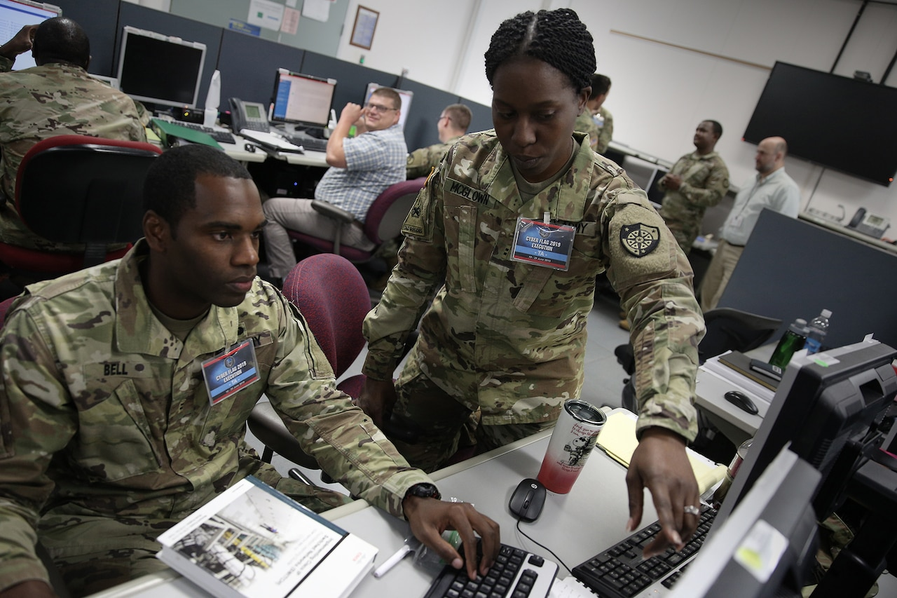 Two uniformed military personnel, a male and a female, work together at a computer.