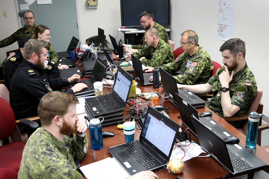 Nine uniformed military personnel, in Canadian military uniforms, sit on either side of a long table and look at laptop computer screens.