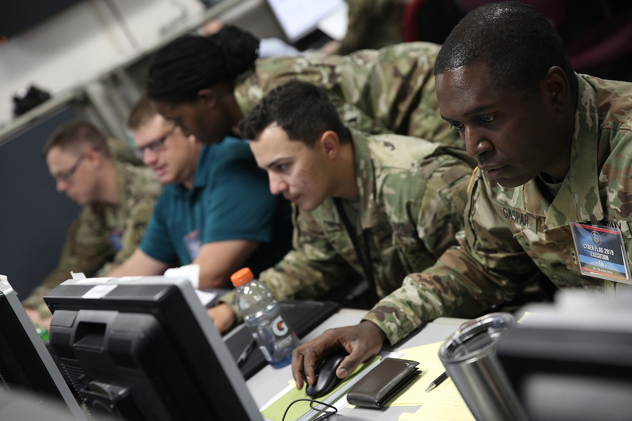 A mix of military and civilian personnel sit at a table and operate computers.  One female service member is standing and looking over the shoulder of the only civilian computer operator.