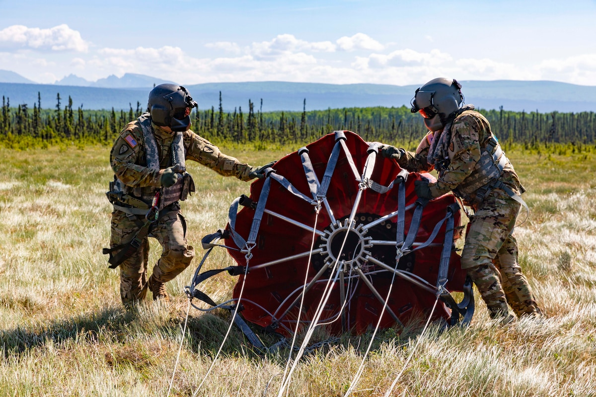 Two soldiers move a large piece of military equipment.