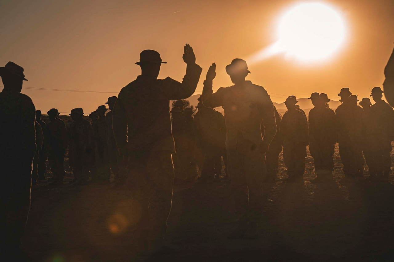 Two Marines hold up their right hands while a large group of Marines surround the two.