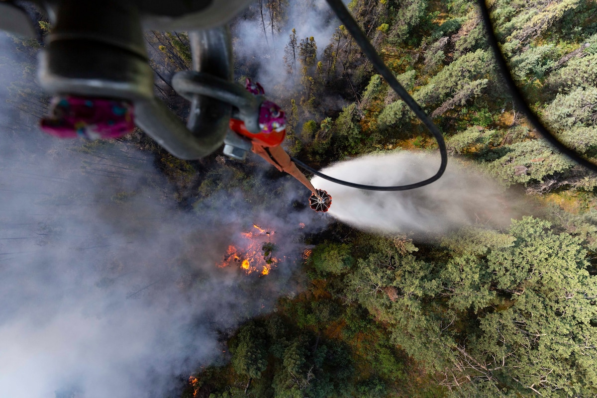 A bucket dangles from a helicopter above a forest wildfire.