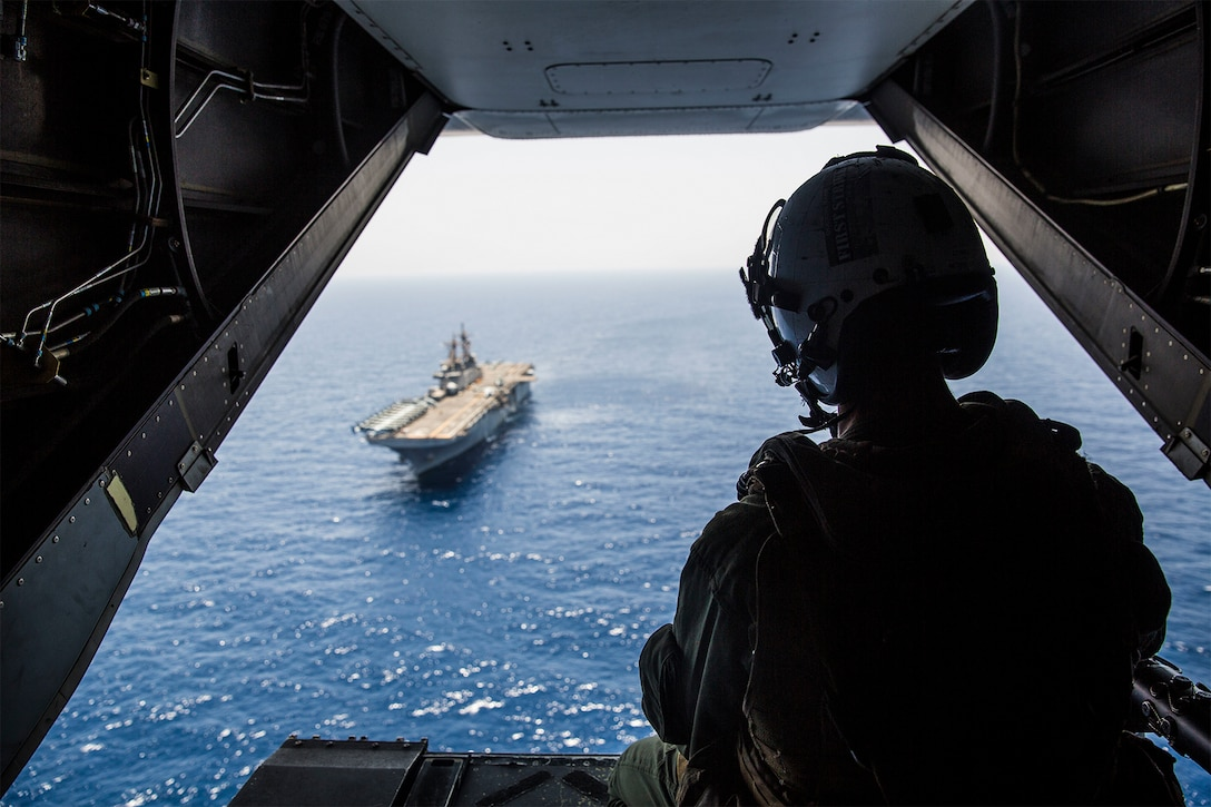 A Marine looks out at the ocean from the back of an aircraft.