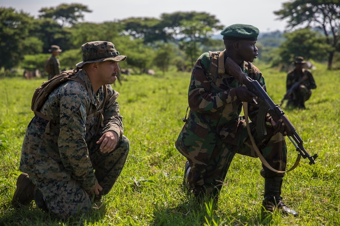 A U.S. Marine with Special Purpose Marine Air-Ground Task Force-Crisis Response-Africa 19.2, Marine Forces Europe and Africa, advises a member of the Uganda People's Defence Force during a theater security cooperation event at Peace Support Operations Training Center Camp Singo, Uganda, June 12, 2019. The Ugandan soldiers trained alongside the U.S. Marines and learned how to properly conduct reconnaissance and improve their logistics and engineering capabilities. (U.S. Marine Corps photo by Cpl. Margaret Gale)