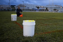 Softball equipment is prepared for the start of the Frozen Rope Challenge on Camp Foster, Okinawa, Japan, July 3, 2019. The challenge was part of the Pacific-Wide Firecracker Softball Skills Challenge; a trial to test a player's skills on how well a player can perform in a specific element of the sport.