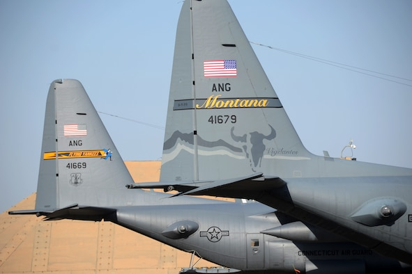 U.S. Air Force C-130s from the Montana and Connecticut Air National Guard currently assigned to the 386th Air Expeditionary Wing sit side by side on the tarmac at Ali Al Salem Air Base, Kuwait, July 3, 2019. The units are currently deployed here providing tactical airlift to the Central Command Area of Responsibility. (U.S. Air National Guard photo by Capt. Stephen Hudson/Released)
