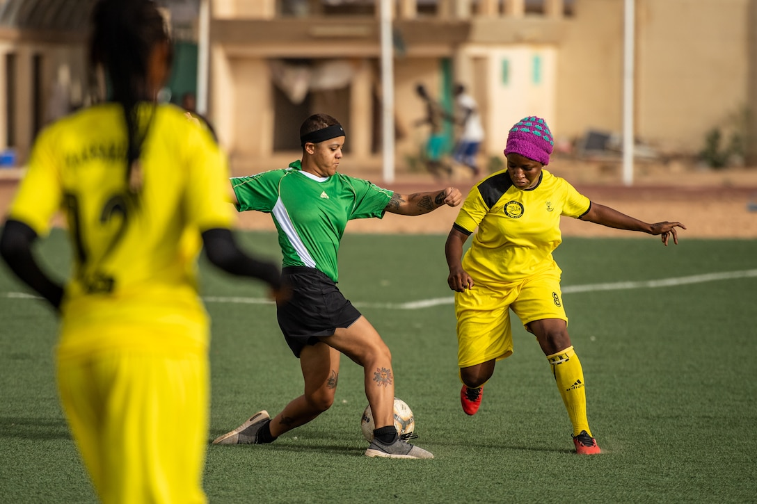 U.S. Air Force Senior Airman Lexis French, 724th Expeditionary Air Base Squadron services flight member, dribbles a soccer ball down a field during a recreational game between Nigerien Air Base 201 and the Nassara Athletic Club Women's Soccer Team at the Agadez Sports Stadium in Agadez, Niger, July 5, 2019. The civil affairs team held the game to build rapport and promote positive sentiment between the local community and AB 201 personnel. (U.S. Air Force photo by Staff Sgt. Devin Boyer)