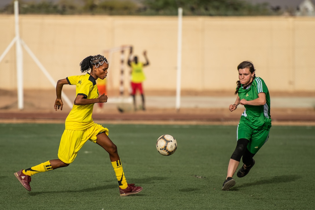 A player from the Nassara Athletic Club Women's Soccer Team, and U.S. Air Force Airman 1st Class Hannah Stublar 31st Expeditionary Red Horse Squadron member, rush to the ball during a recreational game between Nigerien Air Base 201 and the Nassara Athletic Club Women's Soccer Team at the Agadez Sports Stadium in Agadez, Niger, July 5, 2019. The civil affairs team held the game to build rapport and promote positive sentiment between the local community and AB 201 personnel. (U.S. Air Force photo by Staff Sgt. Devin Boyer)