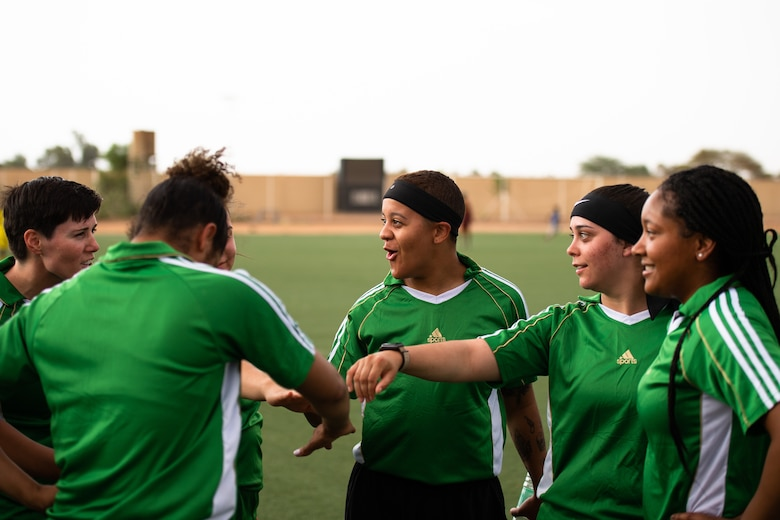 U.S. Air Force Airmen deployed to Nigerien Air Base 201 perform a huddle during a recreational game between Nigerien Air Base 201 and the Nassara Athletic Club Women's Soccer Team at the Agadez Sports Stadium in Agadez, Niger, July 5, 2019. The civil affairs team held the game to build rapport and promote positive sentiment between the local community and AB 201 personnel. (U.S. Air Force photo by Staff Sgt. Devin Boyer)