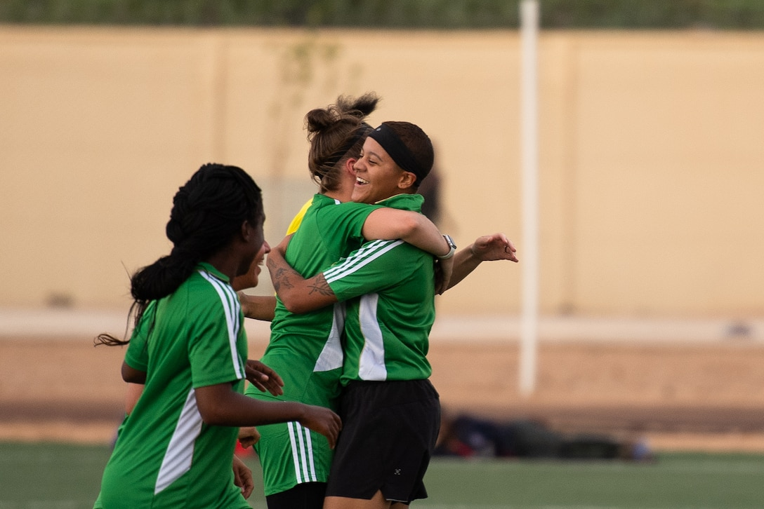 U.S. Air Force Master Sgt. Heather Dragon, 724th Expeditionary Air Base Squadron personnel support for contingency operations member, left, embraces Senior Airman Lexis French, 724th EABS services member, right, after scoring a goal during a recreational game between Nigerien Air Base 201 and the Nassara Athletic Club Women's Soccer Team at the Agadez Sports Stadium in Agadez, Niger, July 5, 2019. The civil affairs team held the game to build rapport and promote positive sentiment between the local community and AB 201 personnel. (U.S. Air Force photo by Staff Sgt. Devin Boyer)