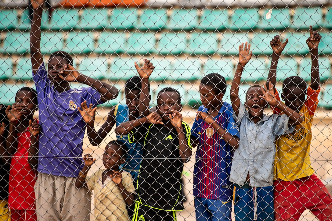 Nigerien children spectate a recreational game between Nigerien Air Base 201 and the Nassara Athletic Club Women's Soccer Team at the Agadez Sports Stadium in Agadez, Niger, July 5, 2019. The civil affairs team held the game to build rapport and promote positive sentiment between the local community and AB 201 personnel. After the game, the base donated 20 soccer balls to the women's team and 10 to the youth development team. (U.S. Air Force photo by Staff Sgt. Devin Boyer)