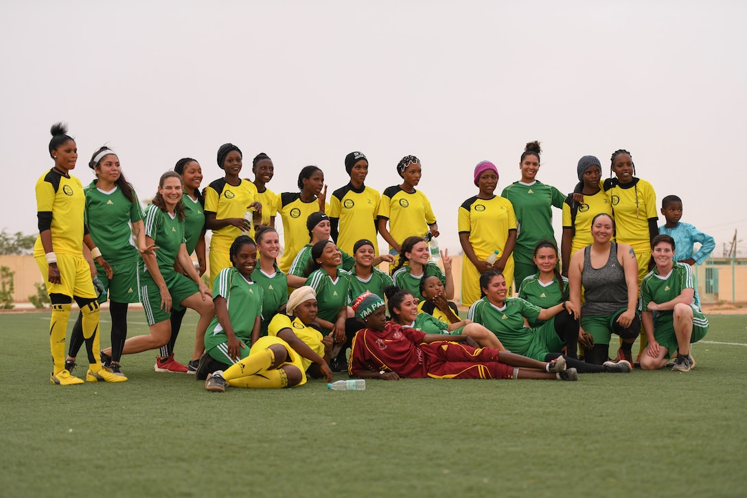 U.S. Air Force women deployed to Nigerien Air Base 201 and the Nassara Athletic Club Women's Soccer Team pose for a photo after a community outreach game at the Agadez Sports Stadium in Agadez, Niger, July 5, 2019. The civil affairs team organized the event that also included the donation of soccer balls to the women's team and youth development team. (U.S. Air Force photo by Senior Airman Lexie West)
