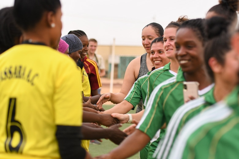 U.S. Air Force women deployed to Nigerien Air Base 201 and the Nassara Athletic Club Women's Soccer Team shake hands after a community outreach game at the Agadez Sports Stadium in Agadez, Niger, July 5, 2019. The civil affairs team held the game to build rapport and promote positive sentiment between the local community and AB 201 personnel. (U.S. Air Force photo by Senior Airman Lexie West)