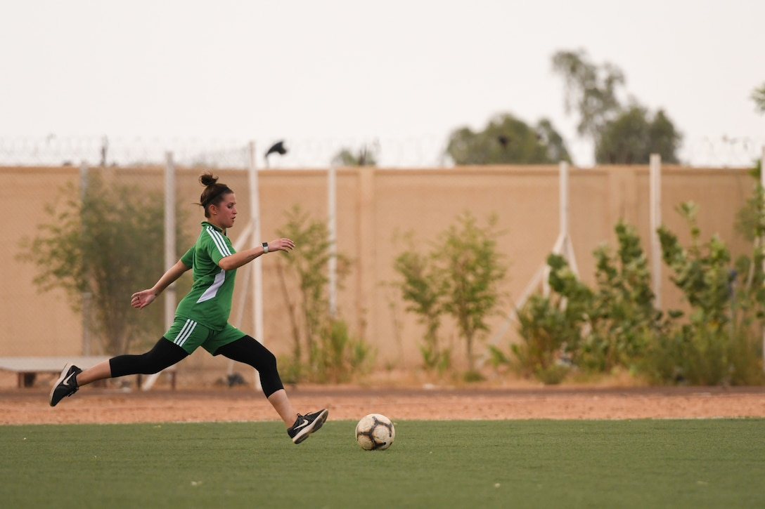 U.S. Air Force Master Sgt. Heather Dragon, 724th Expeditionary Air Base Squadron personnel support for contingency operations member, prepares to strike a soccer ball in a game against the Nassara Athletic Club Women's Soccer Team at the Agadez Sports Stadium in Agadez, Niger, July 5, 2019. The civil affairs team organized the community outreach event that also included the donation of soccer balls to the women's team and youth development team.  (U.S. Air Force photo by Senior Airman Lexie West)