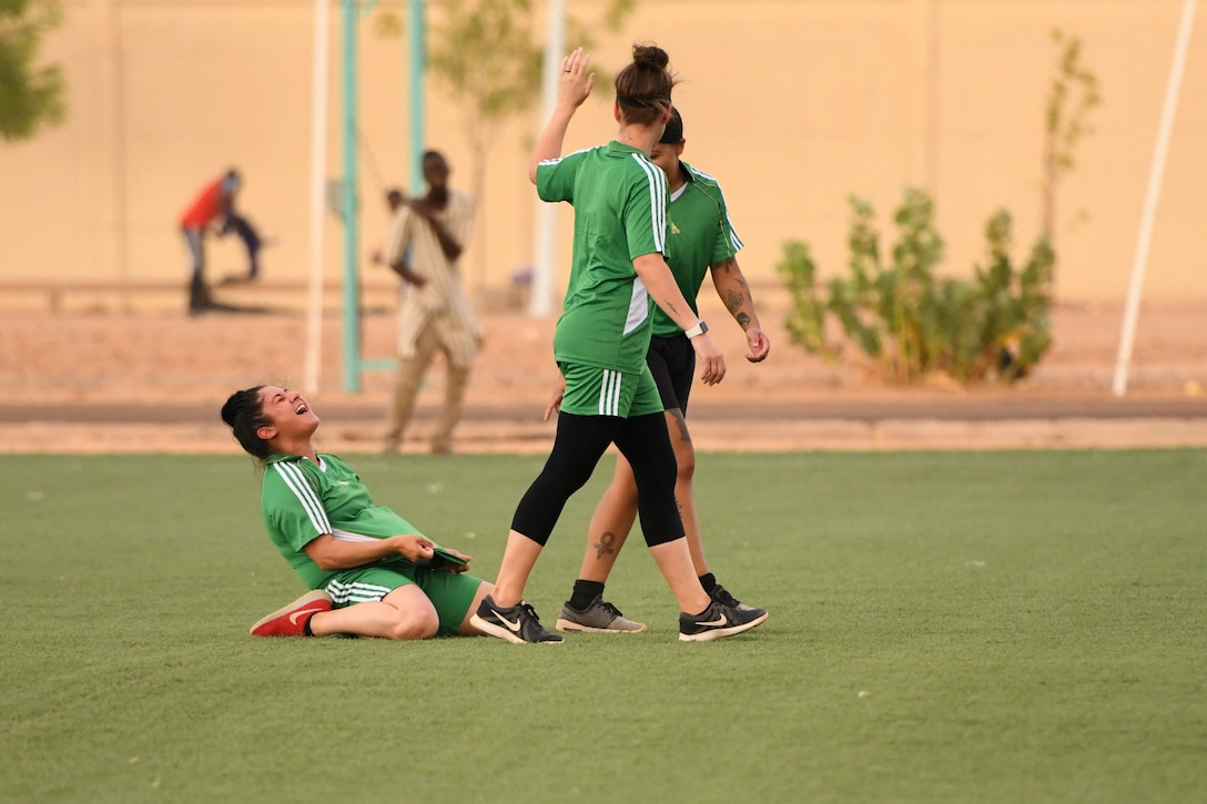 U.S. Air Force Airman First Class Alex Ferrero, 724th Expeditionary Air Base Squadron security forces member, celebrates after scoring a goal during a soccer game against the Nassara Athletic Club Women's Soccer Team at the Agadez Sports Stadium in Agadez, Niger, July 5, 2019. The civil affairs team held the game to build rapport and promote positive sentiment between the local community and Nigerien Air Base 201 personnel.  (U.S. Air Force photo by Senior Airman Lexie West)