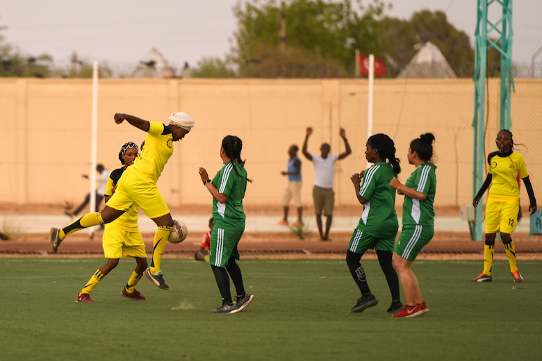 A player from the Nassara Athletic Club Women's Soccer Team knees a soccer ball during a game against U.S. Air Force women from Nigerien Air Base 201 at the Agadez Sports Stadium in Agadez, Niger, July 5, 2019. The civil affairs team held the game to build rapport and promote positive sentiment between the local community and AB 201 personnel.  (U.S. Air Force photo by Senior Airman Lexie West)