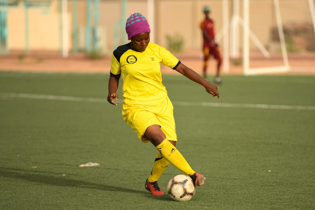 A player from the Nassara Athletic Club Women's Soccer Team maneuvers a soccer ball during a game against U.S. Air Force women from Nigerien Air Base 201 at the Agadez Sports Stadium in Agadez, Niger, July 5, 2019.  The civil affairs team organized the community outreach event that also included the donation of soccer balls to the women's team and youth development team. (U.S. Air Force photo by Senior Airman Lexie West)