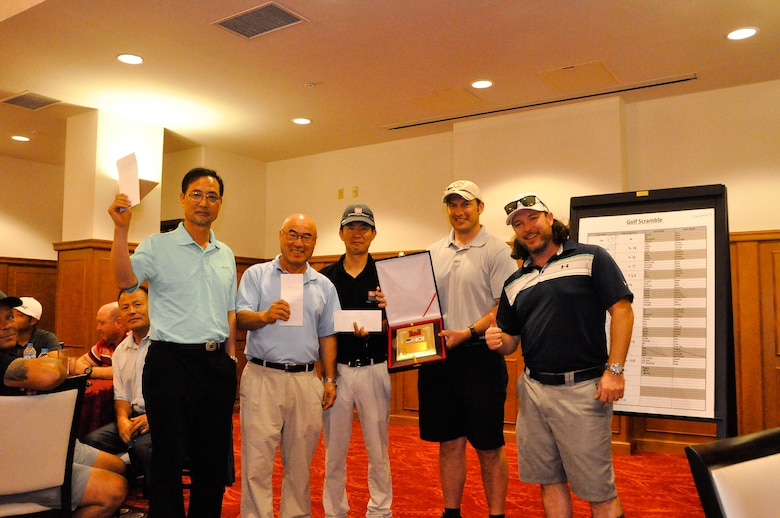 Ross Moore (right), a physical security specialist, stands along with the U.S. Army Corps of Engineers, Far East District, Bi-Annual Golf Tournament winners at the River Bend Golf Course, Camp Humphreys, South Korea, June 26.