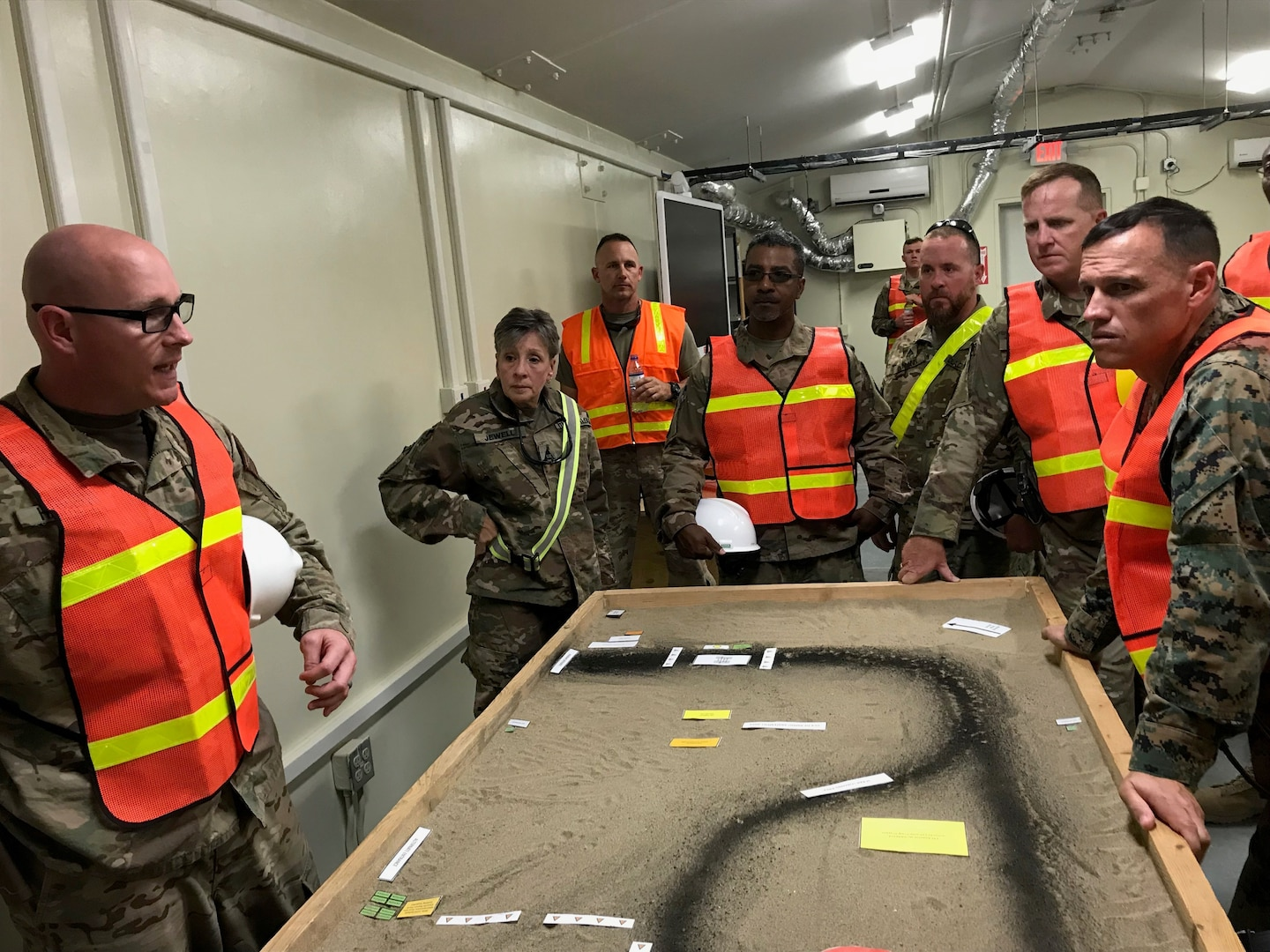 Navy Lt. Cmdr. Steven Harrell, officer-in-charge for DLA Disposition Services in Afghanistan, and Coleen Jewell, area manager, explain mobile expeditionary disposition capabilities and current planning efforts to Marine Brig. Gen. Brian Wolford, the new Bagram Airfield commander, and Army Col. David Raugh, the new Area Support Group-Afghanistan commander.  Pictured from left to right of  Harrell and Jewell are Craig Barrett, outgoing area manager; Jose Montanez, Bagram site chief, Rick Mann, property disposal specialist; Raugh and Wolford.