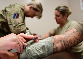 Senior Airman Heather Bell, medical technician with the 911th Aeromedical Evacuation Squadron, and Flight Lt. Lisa Page, medical support officer with the Royal Air Force Leuchars, Scotland, practice bandaging wounds on Capt. Ashley Stough, flight nurse with the 911th AES, and Senior Airman Autumn Maurin, medical technician with the 911th AES, at Fort Indiantown Gap, Pennsylvania, June 18, 2019. This practice session would benefit later in the week as they used these skills during a simulated combat environment. (U.S. Air Force photo by Senior Airman Grace Thomson)