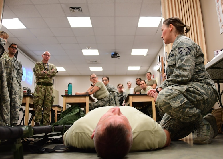 Tech Sgt. Nicole Martin, aerospace medical technician with the 911th Aeromedical Staging Squadron, trains members of the 911th Airlift Wing and the Royal Air Force Leuchars, Scotland, on the proper way to get a patient onto a litter at Fort Indiantown Gap, Pennsylvania, June 19, 2019. Martin showed the Airmen that when putting a patient onto a litter it is important to make sure that a blanket be put under them in order to prevent hypothermia and protect their wounds from the elements as they are transported. (U.S. Air Force photo by Senior Airman Grace Thomson)