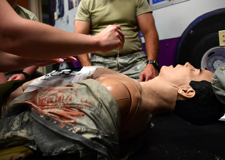 Airmen from the 911th Airlift Wing perform a medical procedure on a mechanical mannequin at Fort Indiantown Gap, Pennsylvania June 19, 2019. During the week-long training at Fort Indiantown Gap, the medical personnel trained on several different procedures using the mechanical mannequins. (U.S. Air Force photo by Senior Airman Grace Thomson)