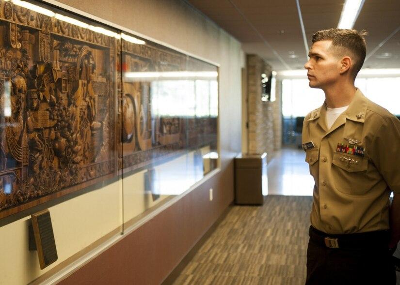 Military man looking at historical wall
