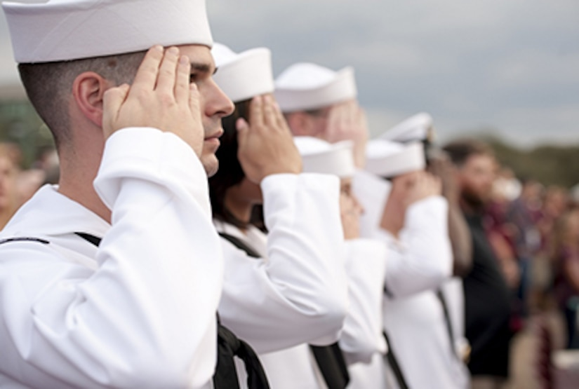 Sailors in white uniform in line saluting