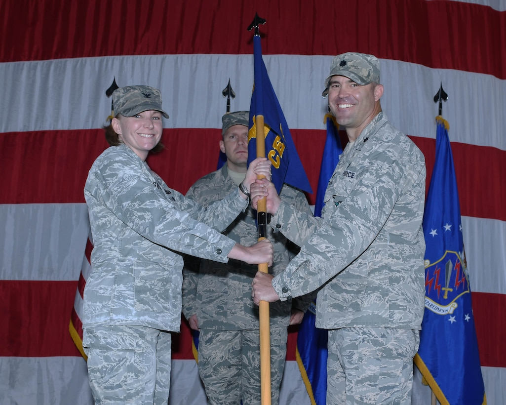 PETERSON AIR FORCE BASE, Colo. – Col. Kirsten Aguilar (left), 21st Mission Support Group commander, presents the guidon to Lt. Col. Timothy Fryar (right), the new 21st Civil Engineer Squadron commander, during a change of command ceremony June 27, 2019 at Peterson Air Force Base, Colorado. The passing of the guidon represents a formal transfer of authority and responsibility from an outgoing commander to an incoming one, ensuring that the unit and its Airmen are never without leadership. (U.S. Air Force photo by Airman 1st Class Andrew J. Bertain)