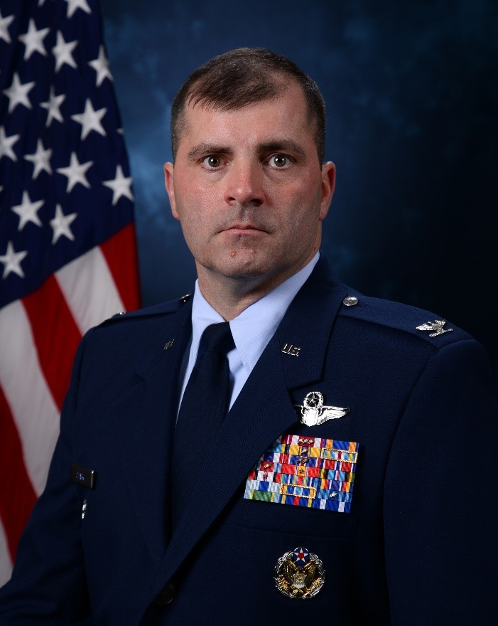 Head and shoulders shot of white male in Air Force Blues posing in front of American flag.