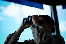 Senior Airman Bailey Hairston, 375th Operational Support Squadron air traffic controller, uses binoculars to look for birds or other hazards that can damage aircraft
