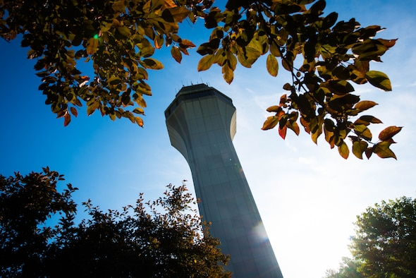 The air traffic control tower is seen through the trees