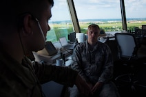 Airman 1st Class Nicklas Hartman talks with Senior Airman Eric Davis, 375th Operational Support Squadron air traffic controllers