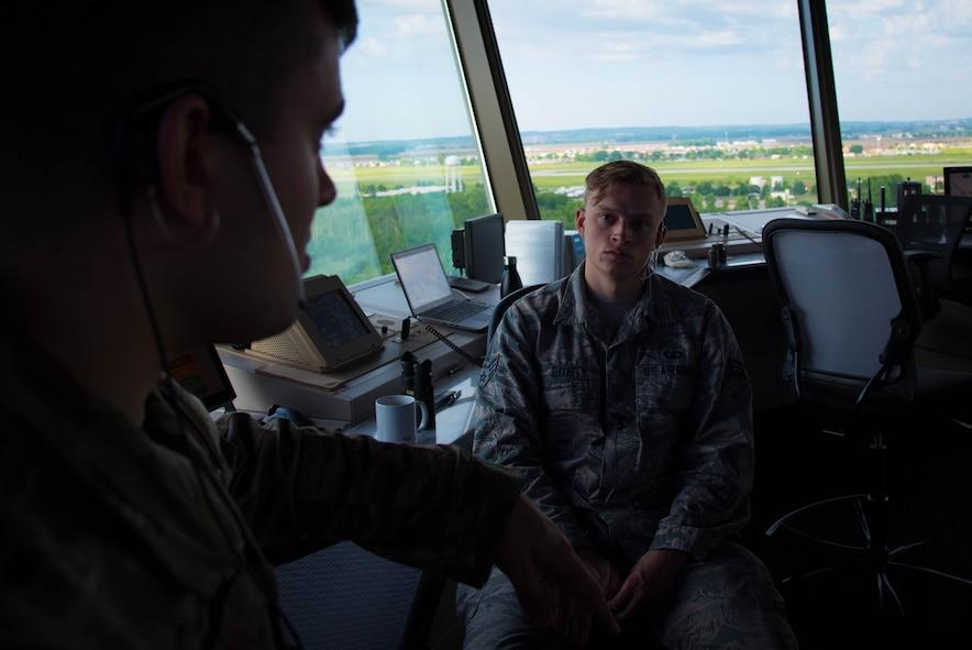 Airman 1st Class Nicklas Hartman talks with Senior Airman Eric Davis, 375th Operational Support Squadron air traffic controllers