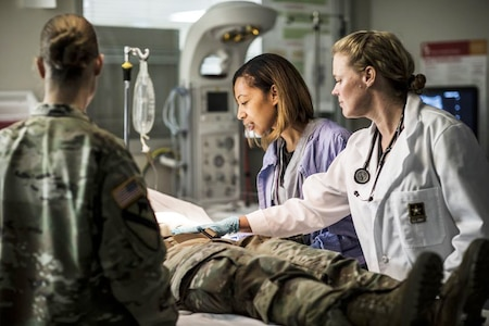 Two doctors with a soldier on the table and one soldier standing by.