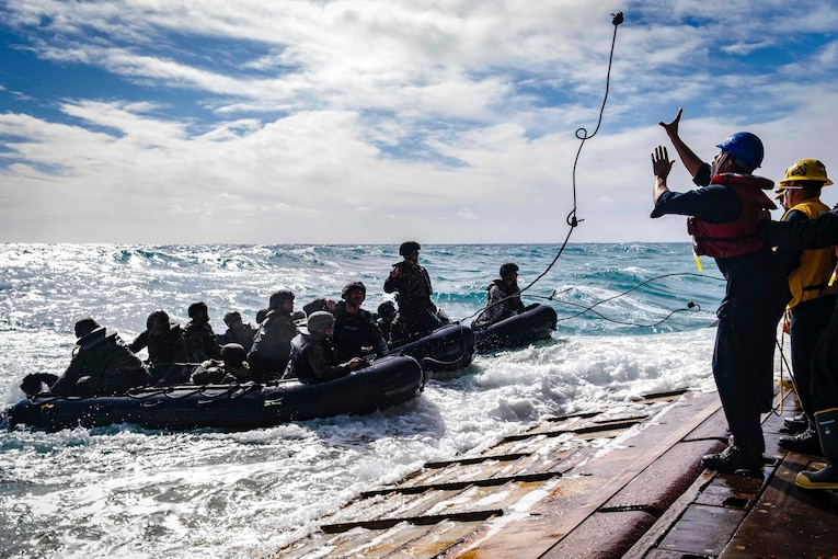 A sailor attempts to catch a rope from Marines in a small boat.