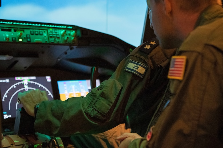 With the help of an U.S. Air Force Airman, an Israeli air force Air Attaché to the United States of America member flies a KC-46A Pegasus flight simulator, July 1, 2019, at Altus Air Force Base, Okla. This was an opportunity to strengthen to U.S.-Israeli bilateral relationship while showcasing the home of the U.S. Air Force's newest and most advanced tanker aircraft. (U.S. Air Force photo by Airman 1st Class Breanna Klemm)