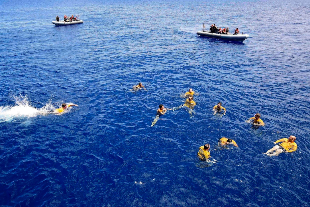 A group of sailors swim in the ocean while two inflatable boats stand watch.