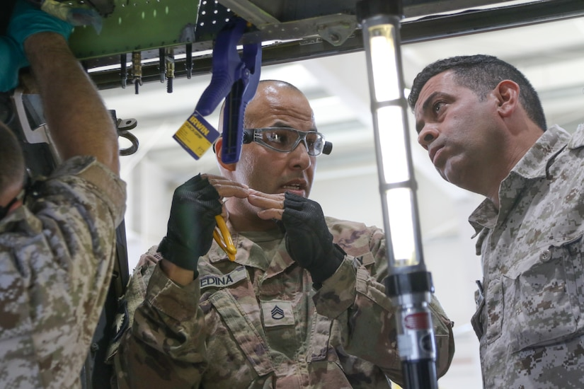 U.S. Army Staff Sgt. Jose Medina, 1106th Aviation Group, explains how fabricated sheet metal should align to the beam of a UH-60 Blackhawk helicopter to 2nd Lt. Raad Alzubi, Royal Jordanian Air Force, during a recent UH-60 Blackhawk subject matter expert exchange at the King Abdullah II Air Base in Amman, Jordan, June 19, 2019.
