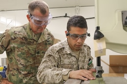 U.S. Army Sgt. 1st Class Douglas Spillers, 34th Infantry Division, monitors the trimming of sheet metal by Sgt. Amer Alamaira, Royal Jordanian Air Force, during a UH-60 Blackhawk subject matter expert exchange at the King Abdullah II Air Base in Amman, Jordan, June 19, 2019.