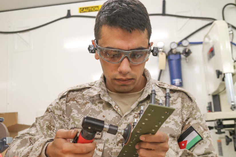 Sgt. Amer Alamaira, Royal Jordanian Air Force, sands down a fabricated sheet metal piece that will be applied to a UH-60 Blackhawk helicopter during a subject matter expert exchange with the U. S. Army's 1106th Aviation Group at the King Abdullah II Air Base in Amman, Jordan, June 19, 2019.
