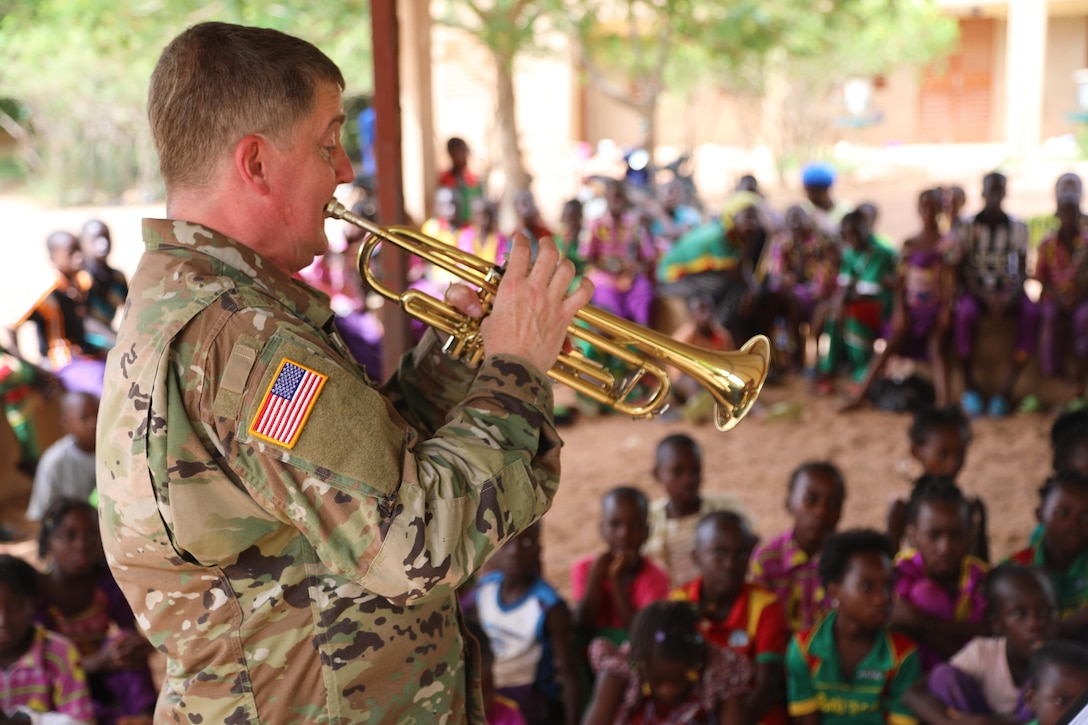 A soldier plays an instrument for children gathered around.
