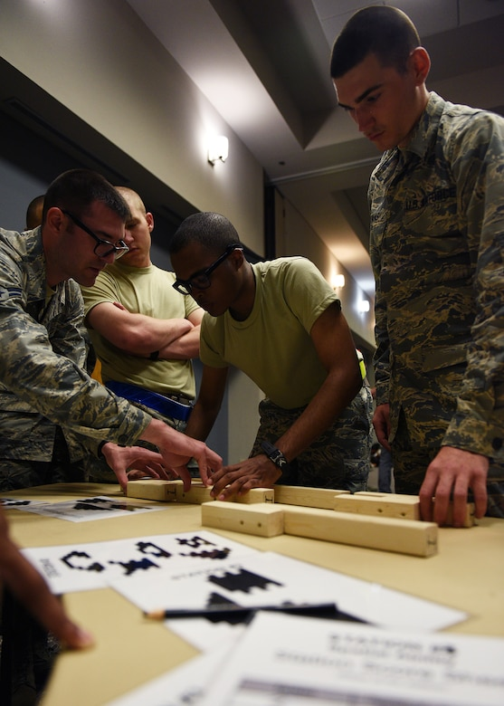 Participants of the Mental Fitness Obstacle Course work to complete a puzzle within the required time limit in conjunction with various callisthenic exercises at the event center on Goodfellow Air Force Base, Texas, July 2, 2019. The course was designed by the 17th Training Group to highlight the link between physical exertion and cognitive tasks for new technical training students. (U.S. Air Force photo by Staff Sgt. Chad Warren/Released)