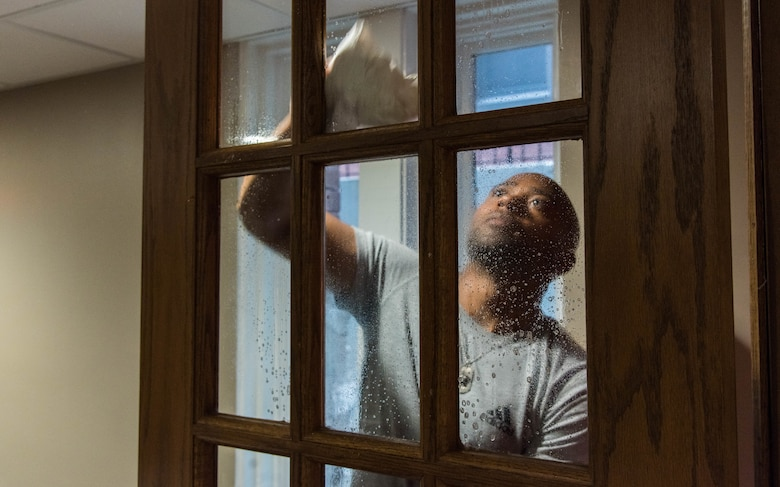 Master Sgt. Johnathan Rias, Air Mobility Command contingency war planning cleans a window inside a Ronald McDonald House in St. Louis