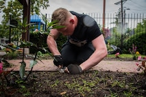 Airman 1st Class Jacob Warren, Air Mobility Command intelligence analyst, removes weeds from a flower bed at a Ronald McDonald House in St. Louis
