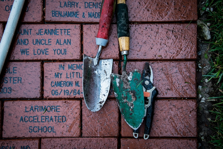 Tools used by volunteers rest on bricks with messages from families who have stayed at the Ronald McDonald house in St. Louis
