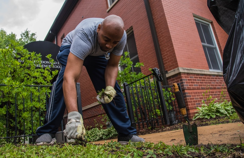 Master Sgt. Johnathan Rias, Air Mobility Command contingency war planning, picks weeds in front of a Ronald McDonald House in St. Louis