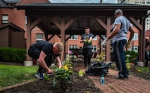 Airmen from Scott Air Force Base clean up a flower bed at the Ronald McDonald House in St. Louis