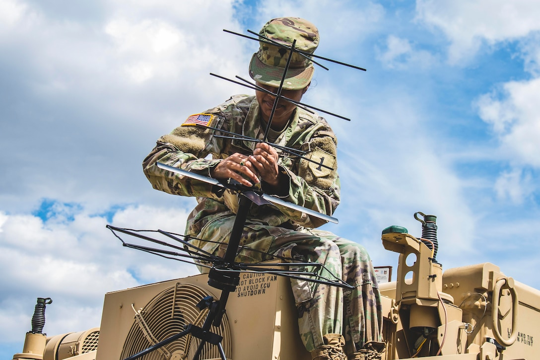 A solider adjusts an antenna on top of a military vehicle.