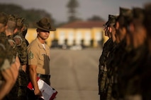 Staff Sgt. Nicolas Campbell, drill master with 1st Recruit Training Battalion, inspects recruits with India Company, 3rd Recruit Training Battalion during a final drill evaluation at Marine Corps Recruit Depot San Diego, June 29.